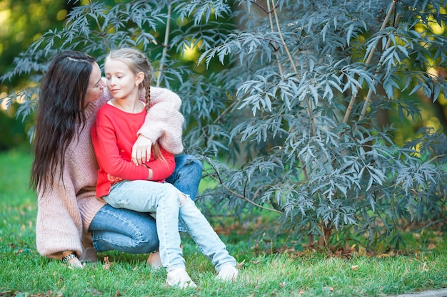 Adorable little girl with young mother in blooming garden on spring day
