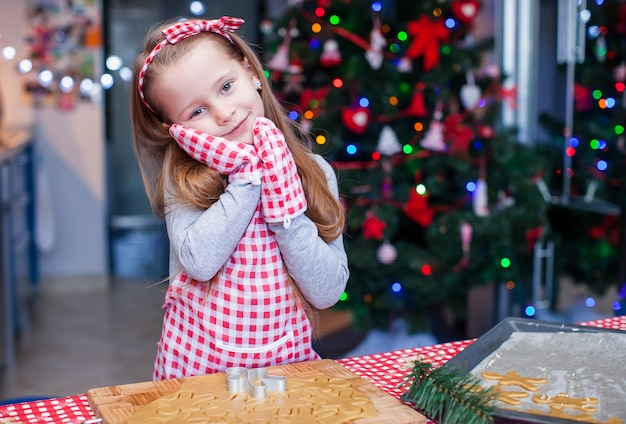 Adorable little girl in wore mittens baking christmas gingerbread cookies
