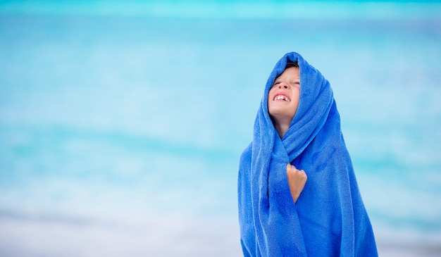 Adorable little girl wrapped in towel at tropical beach after swimming in the sea