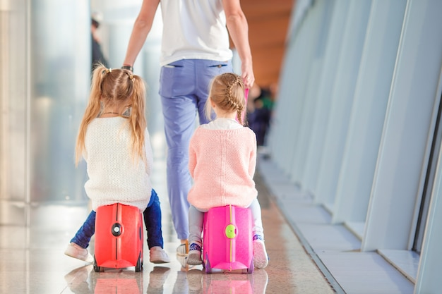 Adorable little girls in airport sitting on suitcase waiting for boarding