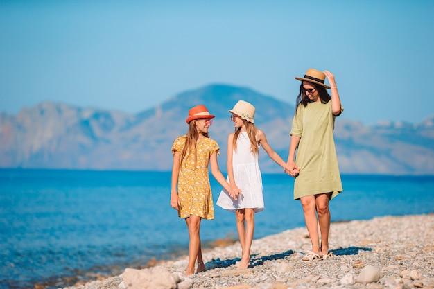 Очаровательные маленькие девочки и молодая мать на тропическом белом пляже