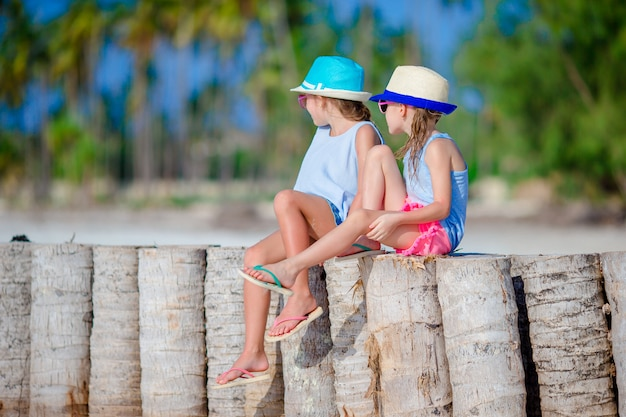 Adorable little girls during summer vacation on the white beach