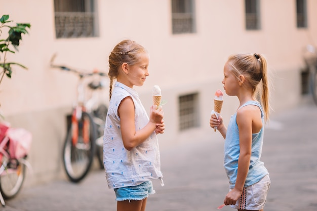 Adorable little girls eating ice-cream outdoors at summer.