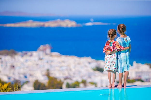Adorable little girls on the edge of outdoor pool with amazing view of famous sights in greece