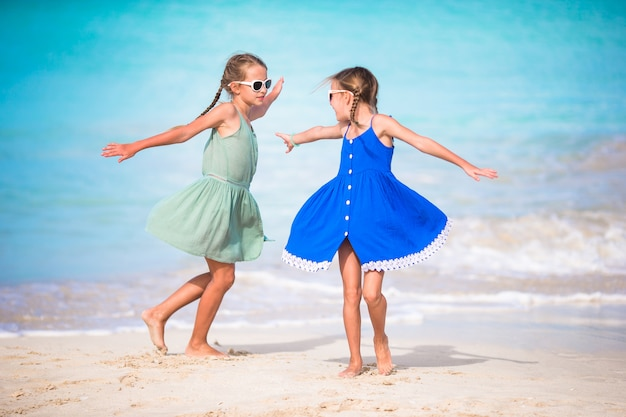 Adorable little girls have a lot of fun on the beach. two beautiful kids are happpy