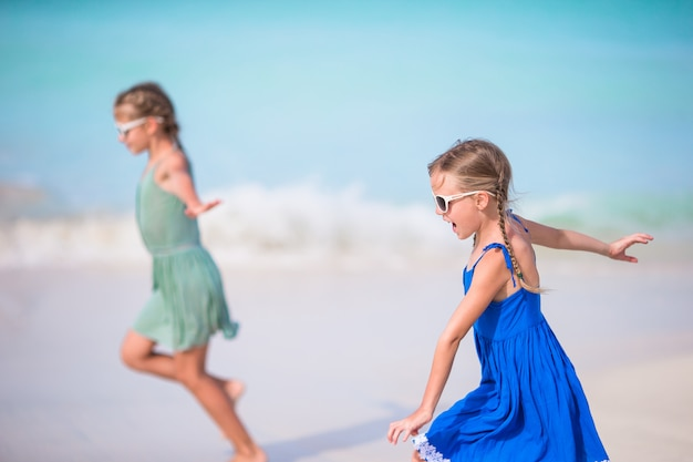 Adorable little girls have a lot of fun on the beach.