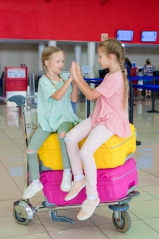 Adorable little girls having fun in airport waiting for boarding