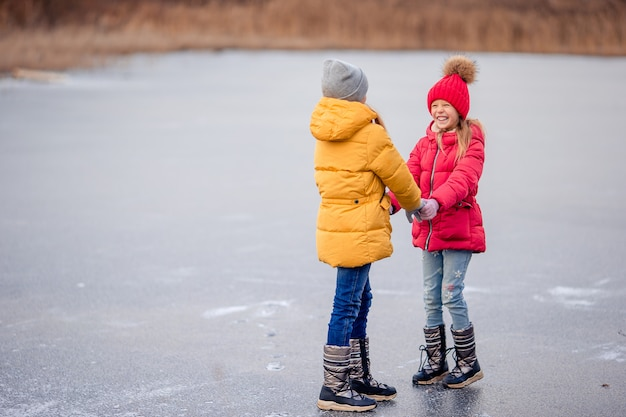 Adorable little girls having fun together on frozen lake