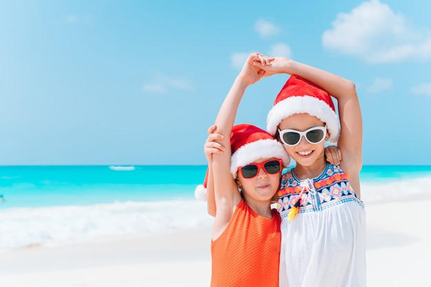 Прелестные маленькие девочки в шляпах санты с морскими звёздами на белом пустом пляже.