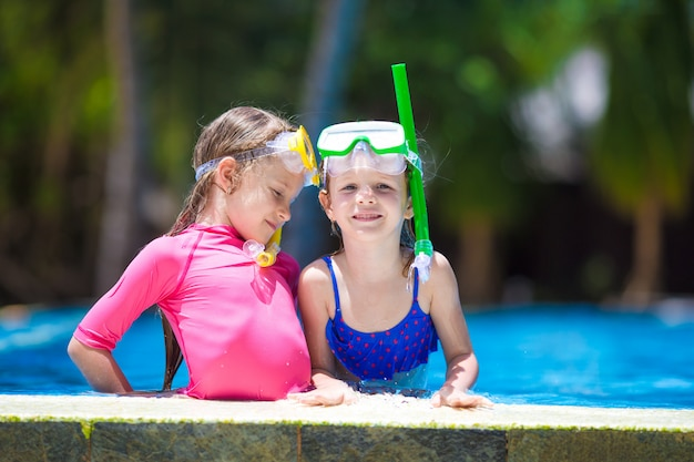 Adorable little girls at mask and goggles in outdoor swimming pool
