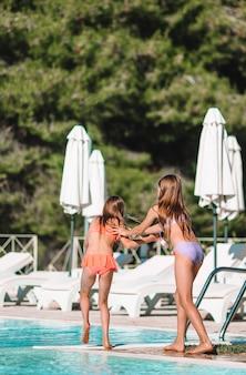 Очаровательные маленькие девочки играют в открытом бассейне на отдыхе