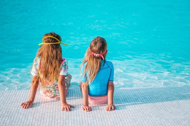 Очаровательные маленькие девочки, играющие в открытом бассейне на отдыхе