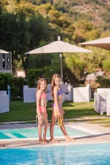 Очаровательные маленькие девочки играют в открытом бассейне