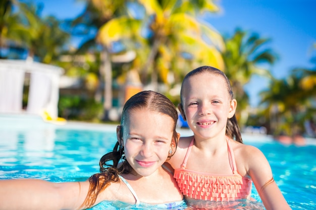 Adorable little girls playing in outdoor swimming pool. cute kids take selfie.
