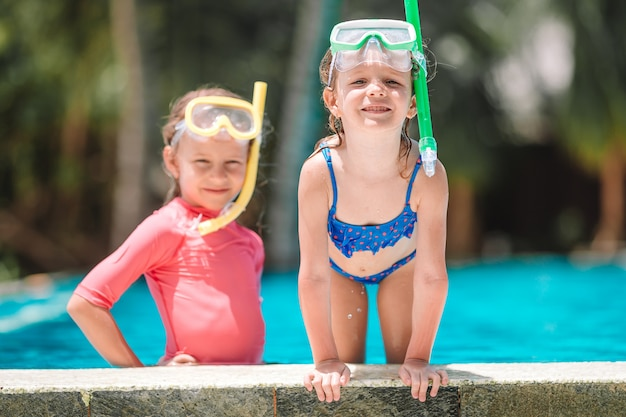 Adorable little girls playing in outdoor swimming pool