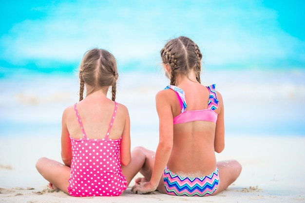 Adorable little girls playing with sand on the beach. back view of kids sitting in shallow water and making a sandcastle