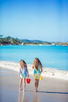 Adorable little girls playing with sand on the beach