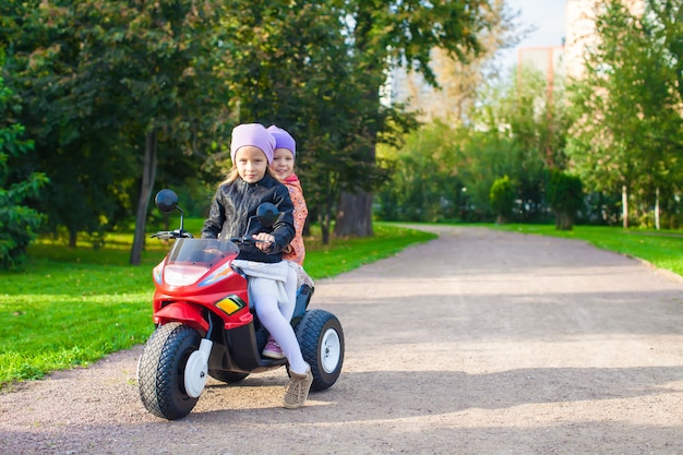 Adorable little girls riding on kid's motobike in the green park
