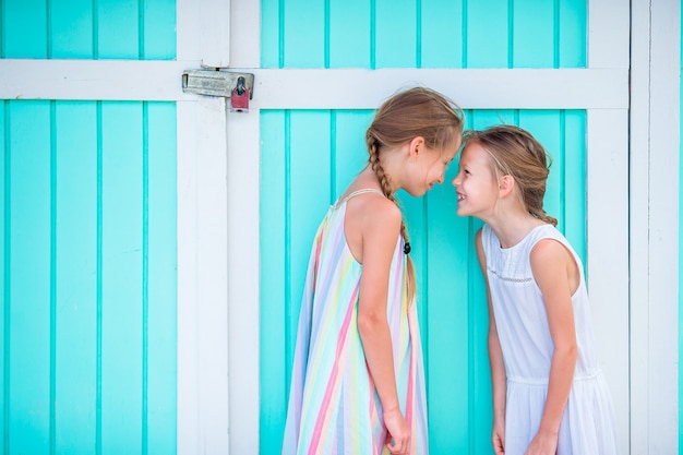 Adorable little girls on summer vacation, traditional colorful caribbean house