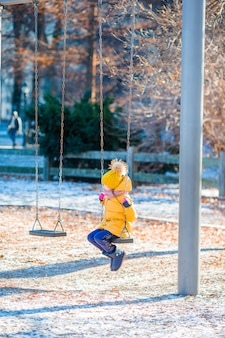 Adorable little girls swings on a swing in central park at new york city