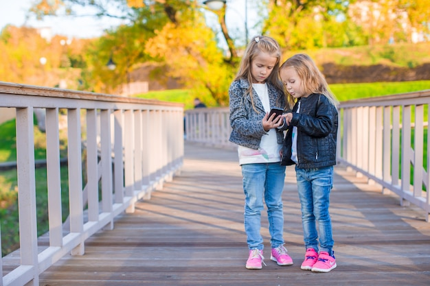 Adorable little girls at warm autumn day outdoors