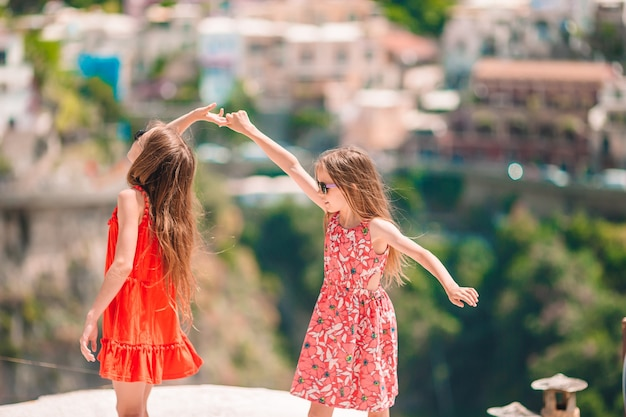 Adorable little girls on warm and sunny summer day in positano town in italy on amalfi coast