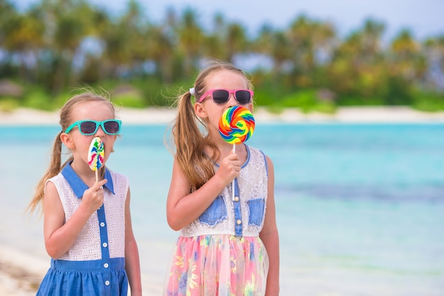 Adorable little girls with bright tasty candies on white beach