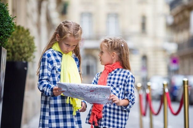 Adorable little girls with map of european city outdoors