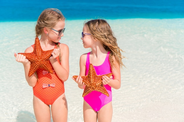 Adorable little girls with starfish on white beach