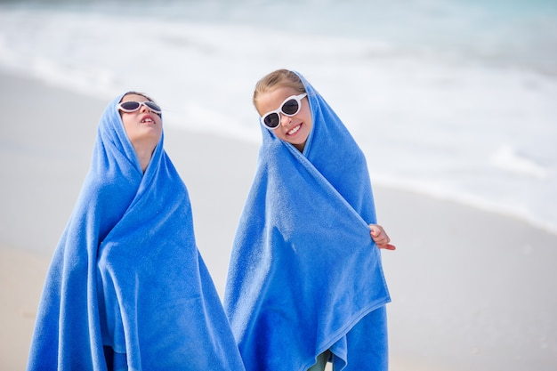 Adorable little girls wrapped in towel at tropical beach after swimming in the sea. two sisters playing on the beach, beach towels