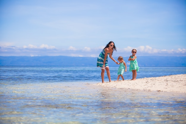 Adorable little girls and young mother have fun on tropical white beach in desert island