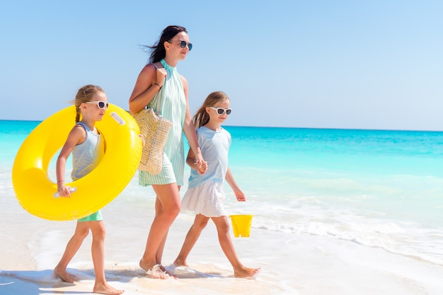 Adorable little girls and young mother on white beach.