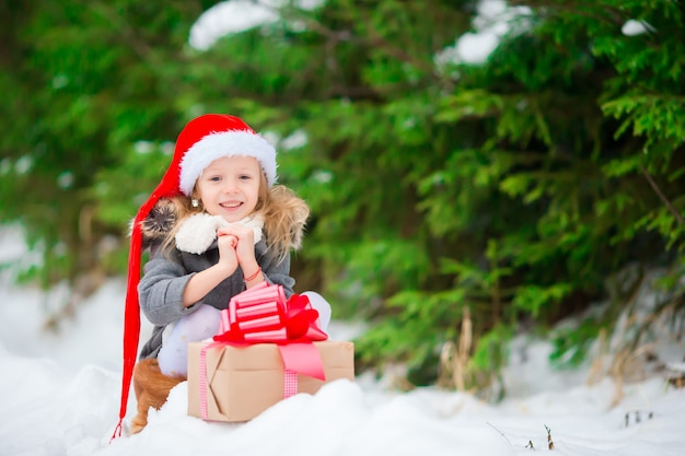 Adorable little gnome with christmas box gift in winter outdoors on xmas eve