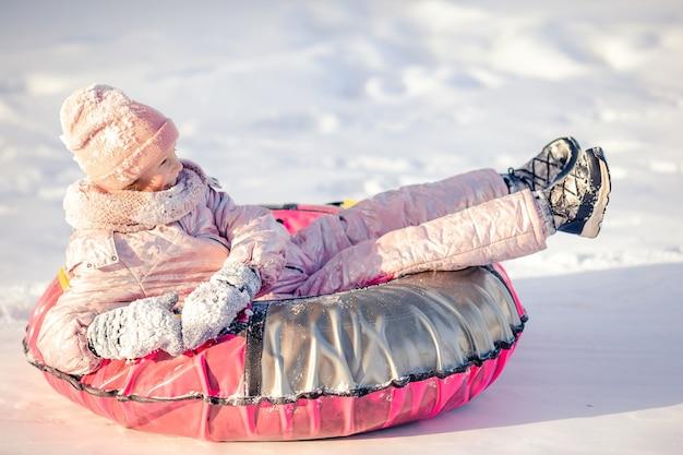 Adorable little happy girl sledding in winter snowy day.