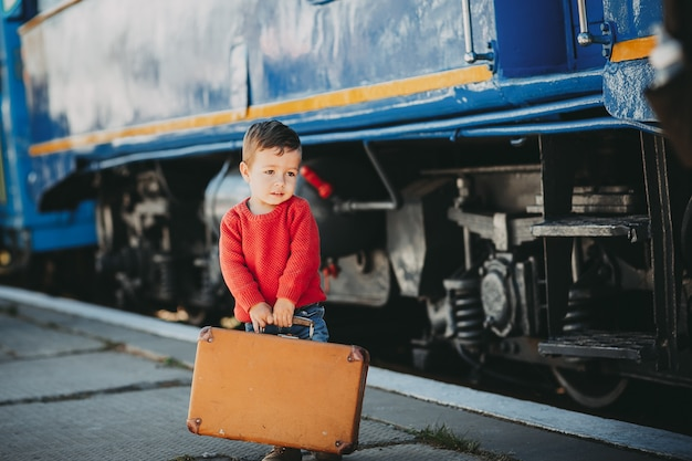 Adorable little kid boy dressed in red sweater on a railway station near train with retro old  brown suitcase.