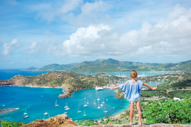 Adorable little kid enjoying the view of picturesque english harbour at antigua in caribbean sea