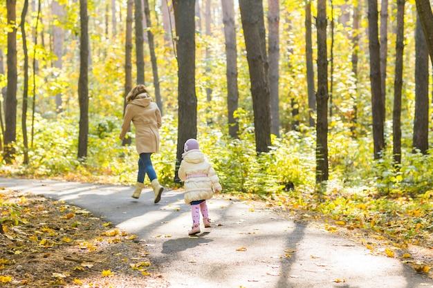 아름 다운가 숲에서 사랑스러운 작은 아이 소녀와 젊은 여자. 어머니에게 실행하는 딸. 가족 초상화, 가을 시즌.