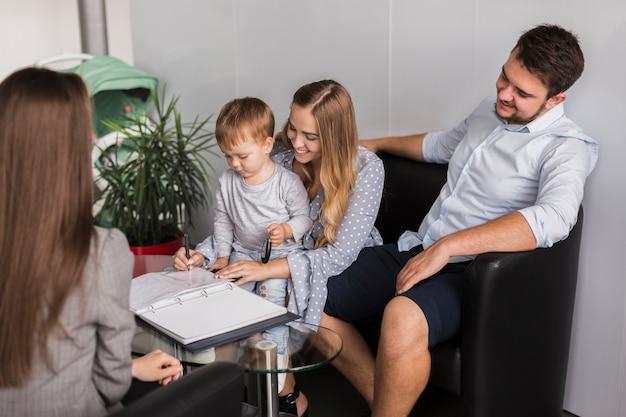 Прелестный маленький ребенок подписывает контракт