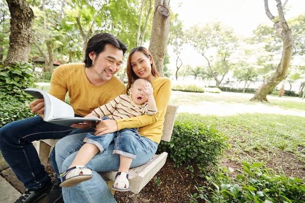 Очаровательный маленький ребенок сидит на коленях у своей матери и зевает, когда ему скучно от отца, читающего ему книгу