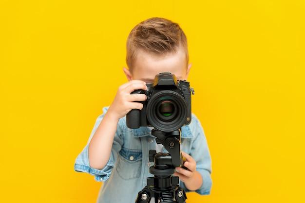 삼각대에 디지털 카메라를 사용하여 사진을 찍는 사랑스러운 작은 아이