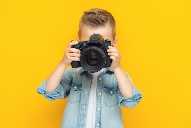디지털 카메라를 사용하여 사진을 찍는 사랑스러운 작은 아이