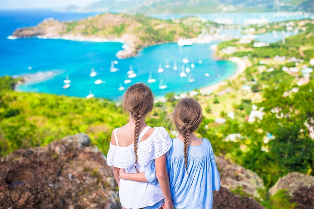 Очаровательные маленькие дети, наслаждаясь видом на живописную английскую гавань в антигуа в карибском море