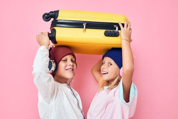 愛らしい小さな子供たちが休暇の準備をしている若い旅行者は背景を分離しました