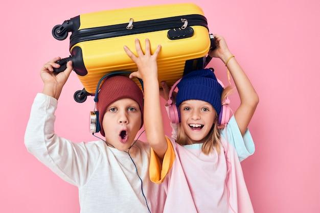 愛らしい小さな子供たちが休暇の準備をしています若い旅行者ピンク色の背景