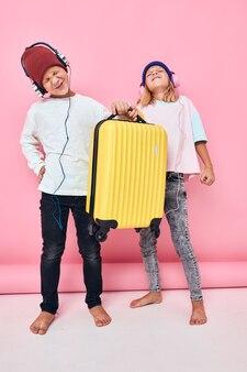 愛らしい小さな子供たちのスタイリッシュな服スーツケースヘッドフォンピンク色の背景