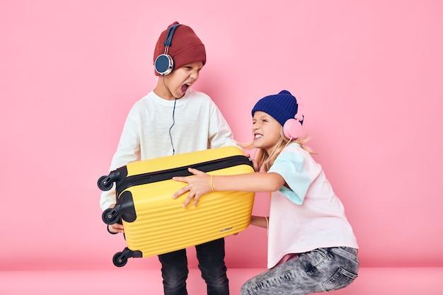 ヘッドフォン付きの愛らしい小さな子供たちの黄色いスーツケース子供時代のライフスタイルのコンセプト