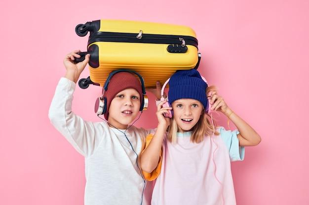 ヘッドフォン分離された背景を持つ愛らしい小さな子供たちの黄色いスーツケース