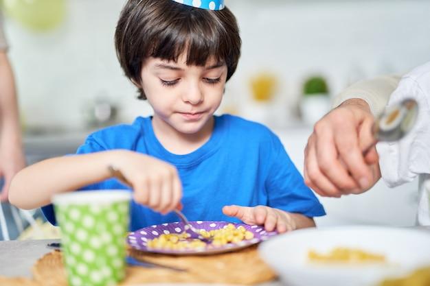 버트데이 모자를 쓴 사랑스러운 라틴 아메리카 소년은 집에서 가족과 함께 생일을 축하하면서 식사를 합니다. 아이, 축하 개념