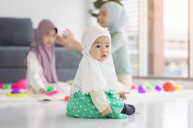 Очаровательная маленькая мусульманская девочка, лежа на полу, глядя на камеру.