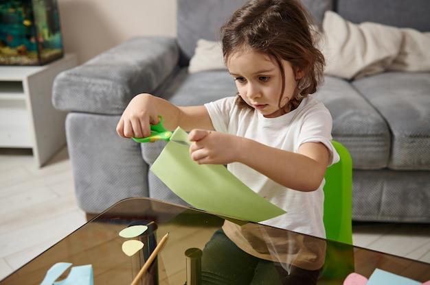 사랑스러운 작은 유치원 소녀는 테이블에 앉아 녹색 종이에서 모양을 절단하는 데 집중했습니다.